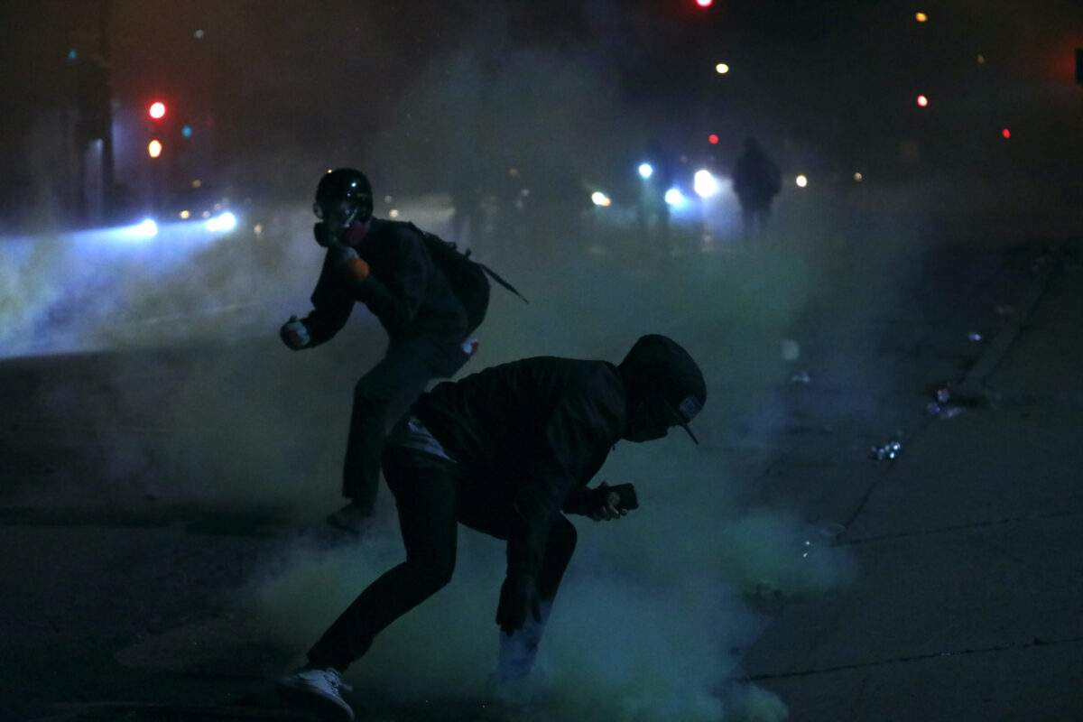 A rioter tries to grab a tear gas canister and lob it back toward the police outside the Minneapolis Police 5th Precinct