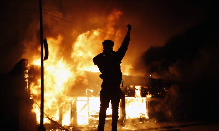 A check-cashing business burns in Minneapolis, Minn., on May 29, 2020. (John Minchillo/AP Photo)