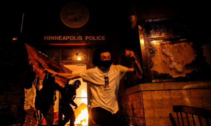Rioters are seen as they set fire to the entrance of a police station as demonstrations continue in Minneapolis, Minnesota, on May 28, 2020. (Carlos Barria/Reuters)
