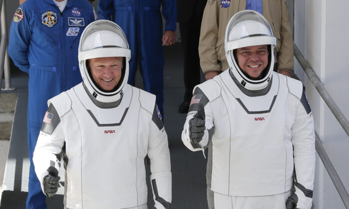 NASA astronauts Douglas Hurley (L) and Robert Behnken walk out of the Neil A. Armstrong Operations and Checkout Building on their way to Pad 39-A, at the Kennedy Space Center in Cape Canaveral, Fla., on May 30, 2020. (John Raoux/AP photo)