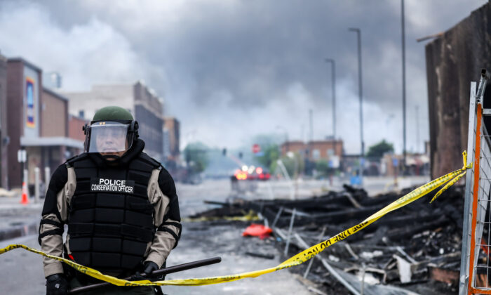 A police officer stands amid smoke and debris as buildings continue to burn in the aftermath of a night of protests and violence following the death of George Floyd, in Minneapolis, Minn., on May 29, 2020. (Charlotte Cuthbertson/The Epoch Times)