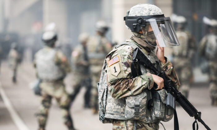 The National Guard sets up near the Lake Street/Midtown metro station as buildings continue to burn in the aftermath of a night of protests and violence following the death of George Floyd, in Minneapolis, Minn., on May 29, 2020. (Charlotte Cuthbertson/The Epoch Times)
