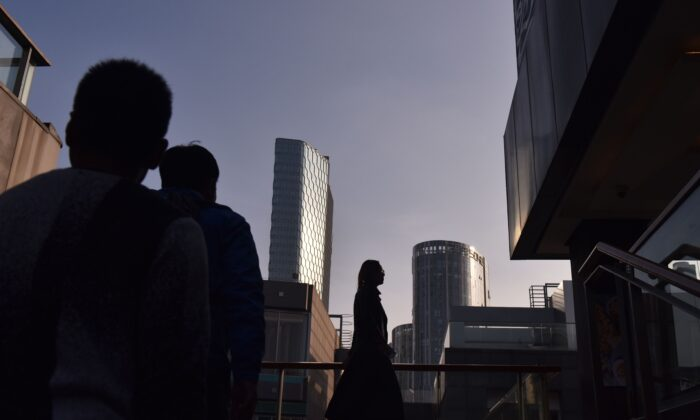 People walk between buildings at a shopping mall in Beijing on October 18, 2018. (GREG BAKER/AFP via Getty Images)