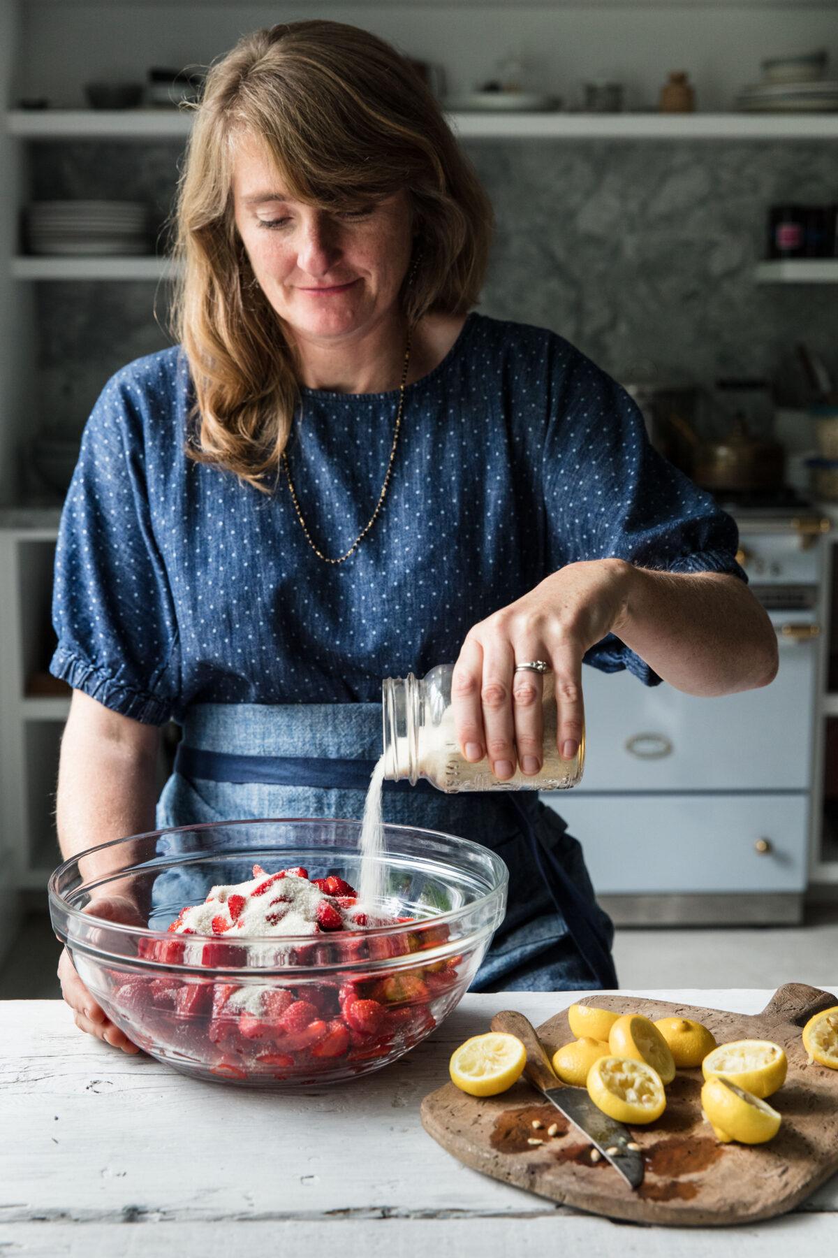 Woman mixes strawberries with sugar and lemon juice to make jam