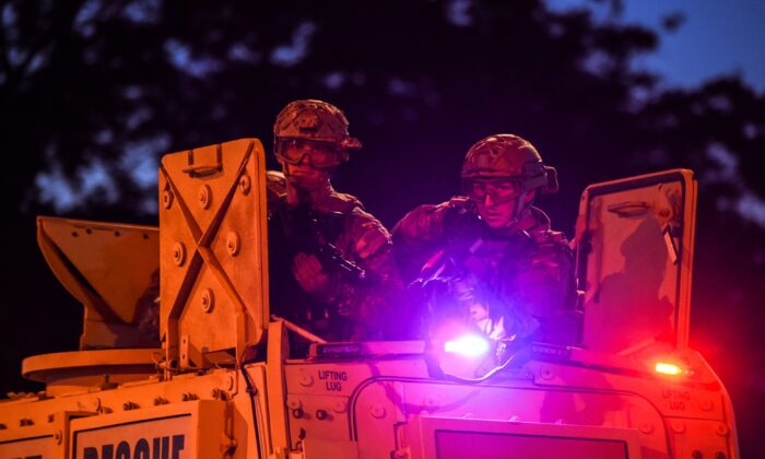 U.S. National Guard soldiers patrol near the 5th police precinct during a demonstration to call for justice for George Floyd, a black man who died while in custody of the Minneapolis police in Minneapolis, Minnesota, on May 30, 2020. (CHANDAN KHANNA/AFP via Getty Images)