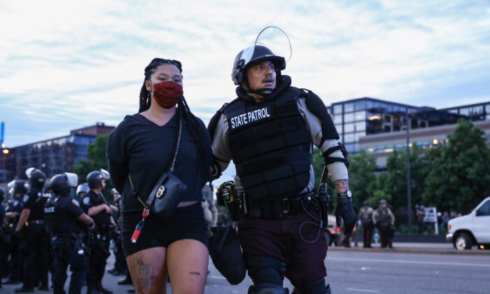 A protester is detained by State Police after staying out beyond the governor's 8 p.m. curfew during the sixth night of protests and violence following the death of George Floyd, in Minneapolis, Minn., on May 31, 2020. (Charlotte Cuthbertson/The Epoch Times)