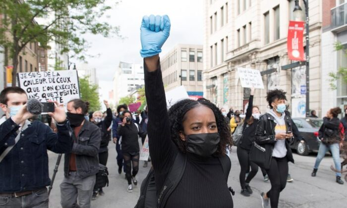 A woman raises her fist during a demonstration calling for justice for George Floyd in Montreal, on May 31, 2020. (Graham Hughes/The Canadian Press)
