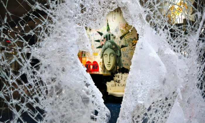 A Statue of Liberty painting is seen through a smashed Dolce and Gabbana store window in SoHo, N.Y., on June 1, 2020. (Mark Lennihan/AP Photo)