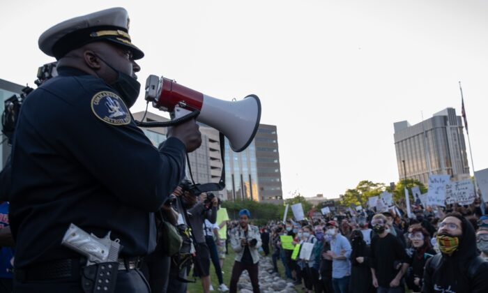 Police officers speak to demonstrators in front of the police station in Detroit, Mich., on May 31, 2020. (Seth Herald/AFP via Getty Images)
