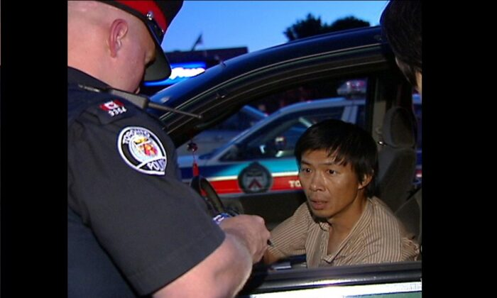 Toronto police question Lu Ping over his delivery of Crescent Chau's anti-Falun Gong tabloid on June 30, 2007, at the Asian Farm grocery store in northeast Toronto. (NTDTV)