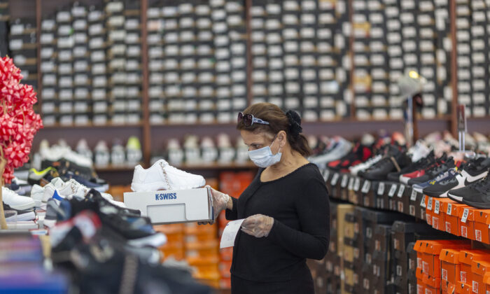 An employee stocks merchandise at a Shoe City store as Los Angeles County retail businesses reopen in Glendale, Calif., on May 27, 2020.    (David McNew/Getty Images)