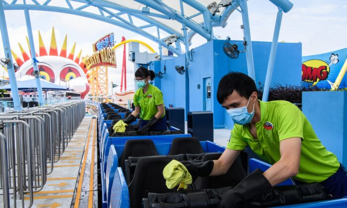 Workers disinfect the Arctic Blast roller coaster ride, as a preventive measure against the COVID-19, at the currently closed local theme park Ocean Park in Hong Kong on May 19, 2020. (Anthony Wallace /AFP via Getty Images)