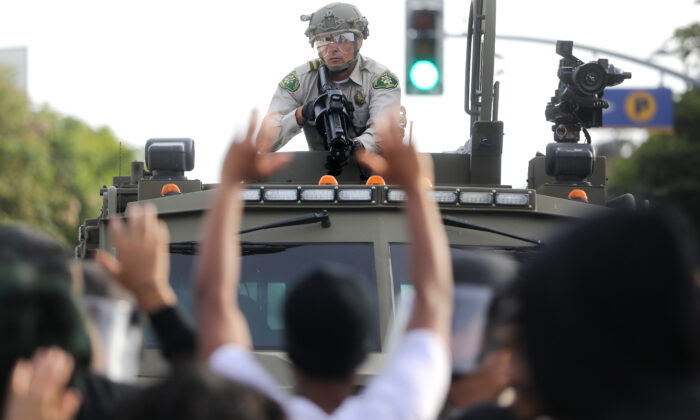 A police officer aims a nonlethal weapon as protesters raise their hands during demonstrations in the aftermath of George Floyd's death  in Santa Monica, Calif., on May 31, 2020. (Mario Tama/Getty Images)