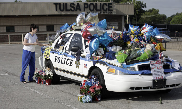 Melanie Dickey, a registered nurse for over 40 years, places an item on a makeshift memorial for Tulsa Police Officers Craig Johnson and Aurash Zarkeshan at Mingo Valley Division on June 30, 2020. (Mike Simons/Tulsa World via AP)