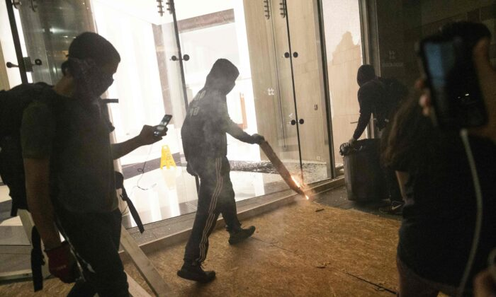 Rioters damage the entrance of an office building in Washington on May 31, 2020. (Roberto Schmidt/AFP via Getty Images)