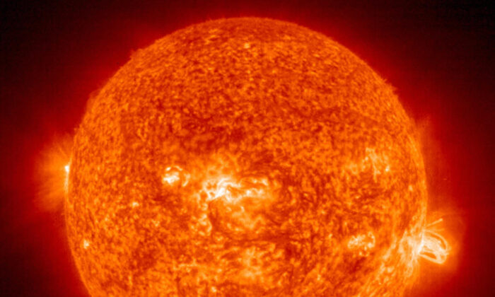 A solar flare (R) erupting from giant sunspot 649. The powerful explosion hurled a coronal mass ejection(CME) into space, but it was directed toward Earth on Aug. 19, 2004.  (HO/AFP via Getty Images)