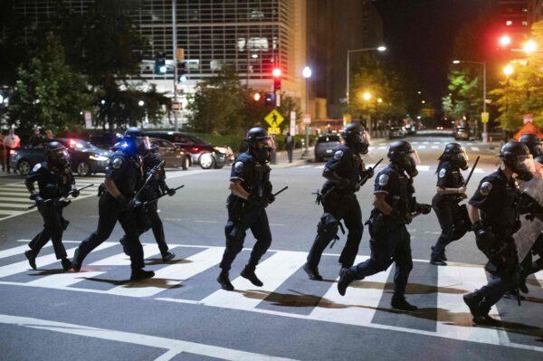 Police run across a street