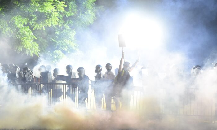 Smoke rises around a protester holding up their hands in front of a row of police during a demonstration against the death of George Floyd at a park near the White House  in Washington on May 31, 2020. (Roberto Schmidt/AFP via Getty Images)