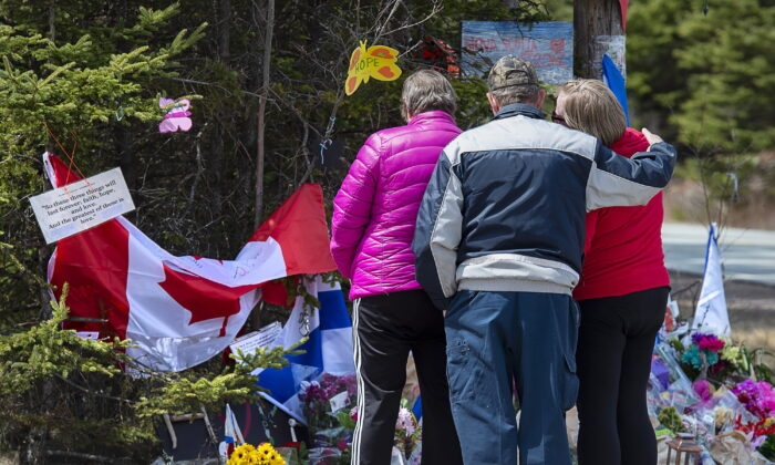 A family pays their respects to victims of the mass killings at a checkpoint on Portapique Road in Portapique, N.S. on April 24, 2020. As pressure mounts on the federal and Nova Scotia governments to call an inquiry into one of the worst mass killings in Canadian history, the country's leading scholar on inquiries says Ottawa and the province should do the right thing and work together on a joint inquest. (Andrew Vaughan/THE CANADIAN PRESS)