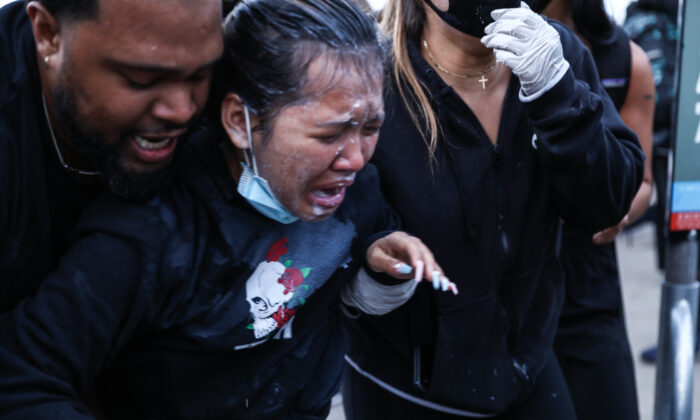 A girl who was pepper sprayed by police is helped by protesters before being detained after staying out beyond the governor's 8 p.m. curfew during the sixth night of protests and violence following the death of George Floyd, in Minneapolis, Minn., on May 31, 2020. (Charlotte Cuthbertson/The Epoch Times)