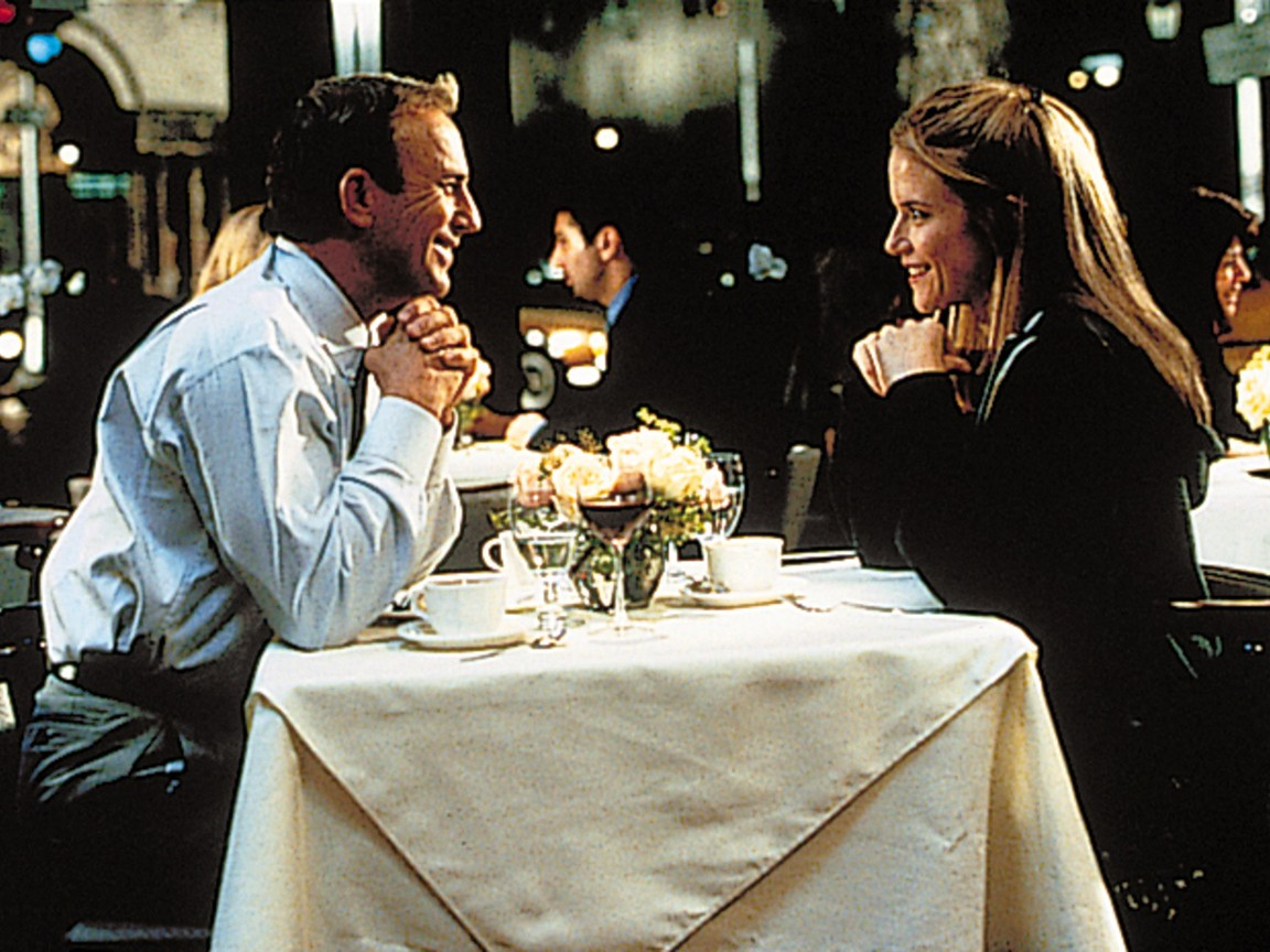 """man and woman sitting at restaurant table in """"For Love of the Game"""""""