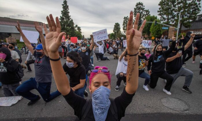 Demonstrators hold their hands up while they kneel on the street during a protest over the death of George Floyd in Anaheim, Calif., on June 1, 2020. (Apu Gomes/AFP via Getty Images)