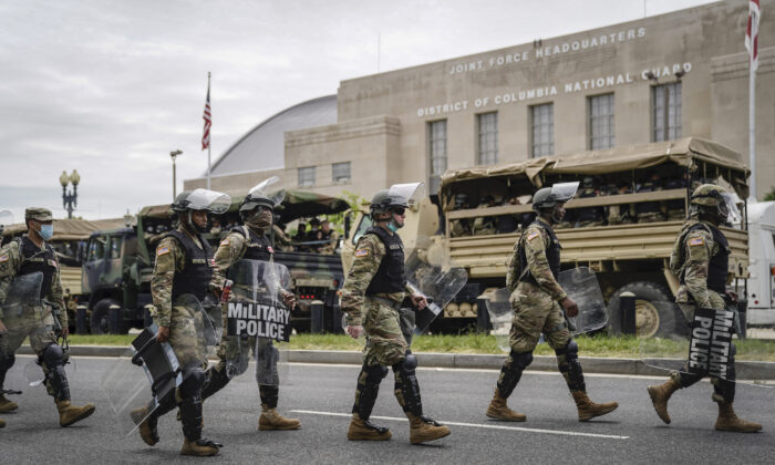 Troops load up into personnel carriers to take them toward the city from the Joint Force Headquarters of the D.C. National Guard in Washington on June 2, 2020. (Drew Angerer/Getty Images)