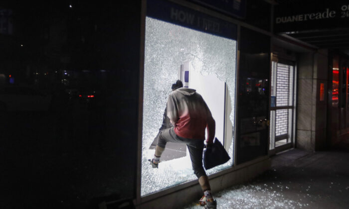 A person enters a store through a broken window, in New York City, New York, on June 1, 2020. (AP Photo/Frank Franklin II)