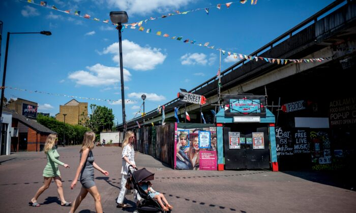People walk past a closed street food and live music venue in Portobello Market in west London on June 1, 2020. (Tolga Akmen/AFP via Getty Images)