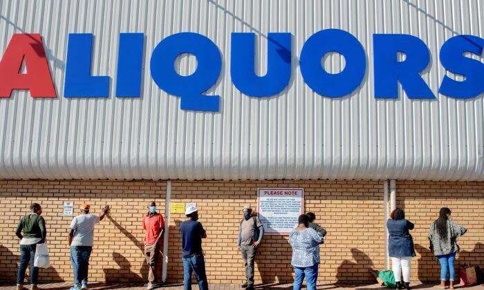 People queue outside a liquor store at the Alexandra mall, in Alexandra, Johannesburg, on June 1, 2020. (Luca Sola/AFP via Getty Images)