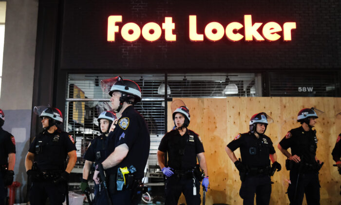 Police stand guard near looted stores during a night of protests and vandalism over the death of George Floyd in New York City on June 1, 2020. (Spencer Platt/Getty Images)