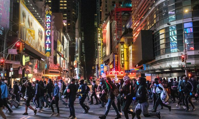 Protesters rush past Times Square after 11 p.m. as a curfew started in New York on June 1, 2020. (John Moore/Getty Images)