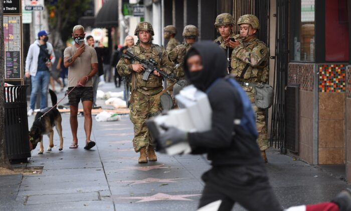 A looter carrying boxes of shoes run past National Guard soldiers in Hollywood, Calif., on June 1, 2020. (Robyn Beck/AFP via Getty Images)