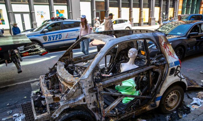 A mannequin sits in a burned police vehicle in the Soho neighborhood of Manhattan in New York City, N.Y., on June 1, 2020. (John Moore/Getty Images)