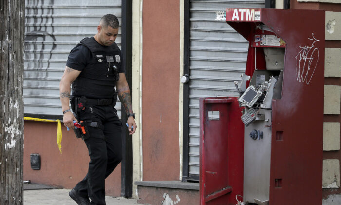 A member of the Philadelphia bomb squad surveys the scene after an ATM machine was blown-up at 2207 N. 2nd Street in Phil., Pa. on June 2, 2020. (David Maialetti/The Philadelphia Inquirer via AP)