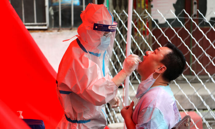 A medical worker takes a swab sample from a resident to be tested for the CCP virus on a street in Mudanjiang, China, on June 3, 2020. (STR/AFP via Getty Images)