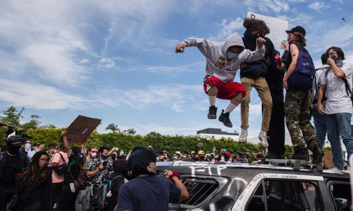 Demonstrators jump on a damaged police vehicle in Los Angeles on May 30, 2020, during a protest following the death of George Floyd. (Ariana Drehsler/AFP via Getty Images)