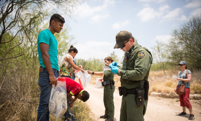 Border Patrol Agents have aliens remove their shoelaces and belongings before loading them in a van for transport in Hidalgo County, Texas, on May 26, 2017.  Prosecutions for immigration crime have remained relatively high, as most prosecutions have plummeted as a result of the pandemic. (Benjamin Chasteen/The Epoch Times)