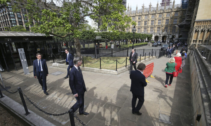 UK lawmakers including Leader of the House of Commons Jacob Rees-Mogg, center left, queue outside the Houses of Commons in Westminster, London on June 2, 2020. (Jonathan Brady/PA via AP)