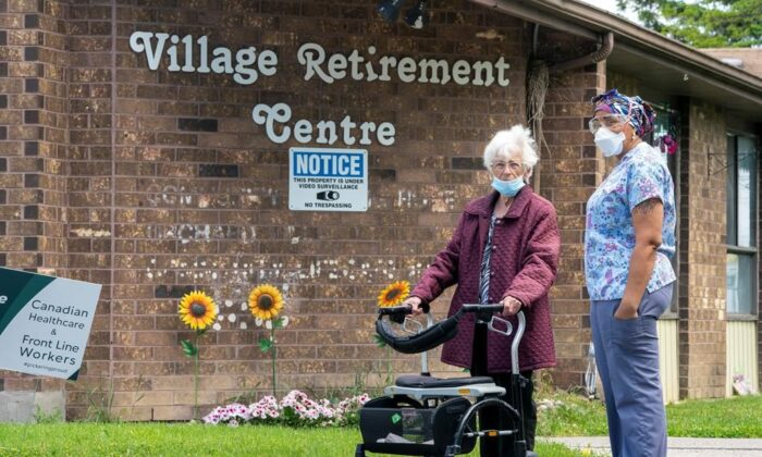 A resident and a worker watch as 150 nursing union members show support at rchard Villa Long-Term Care in Pickering, Ontario on June 1, 2020. (Frank Gunn/The Canadian Press)