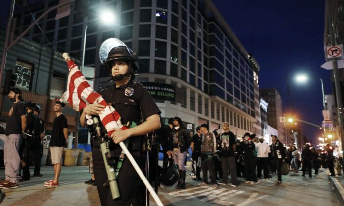 Protesters stand handcuffed under arrest after curfew as a police officer carries away an American flag in Los Angeles, Calif. on June 2, 2020. (Mario Tama/Getty Images)
