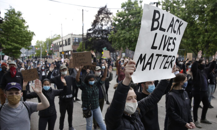 People hold up placards to protest over the death of George Floyd outside the Seattle Police Department's East Precinct in Seattle, Washington on June 2, 2020. (Jason Redmond/AFP via Getty Images)