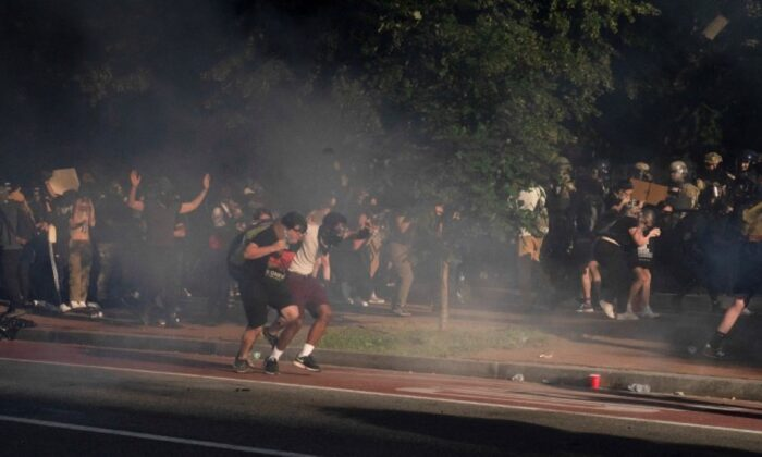 Protestors run as riot police fire crowd control devices and move on demonstrators to clear Lafayette Park and the area around it across from the White House in Washington June 1, 2020. (Ken Cedeno/Reuters)
