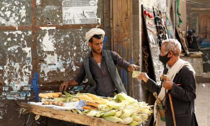A man wearing a protective mask buys corn from a street vendor at a market amid novel coronavirus spread concerns in the old quarter of Sanaa, Yemen on June 2, 2020. (Khaled Abdullah/Reuters)