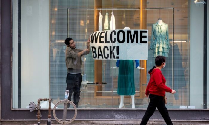 An employee at Zara puts up a sign during a phased reopening from COVID-19 restrictions in Toronto on May 19, 2020. (Carlos Osorio/REUTERS/File Photo)