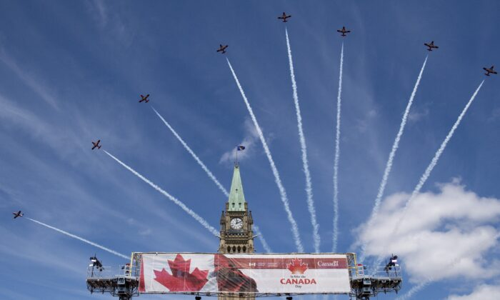 The Canadian Forces Snowbirds fly past the Peace Tower during Canada Day celebrations on Parliament Hill on July 1, 2019. (The Canadian Press/Justin Tang)