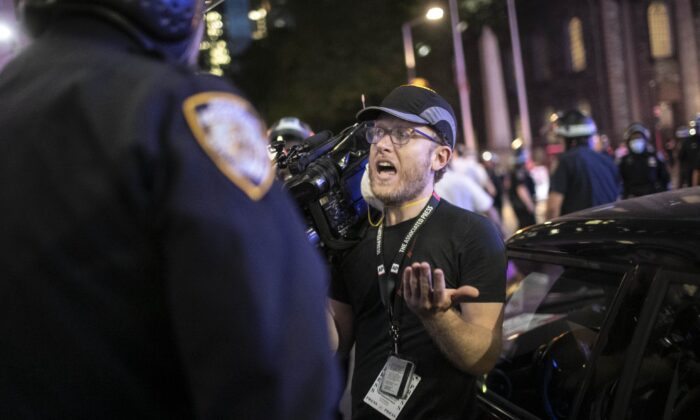 """Associated Press videojournalist Robert Bumsted reminds a police officer that the press are considered """"essential workers"""" and are allowed to be on the streets despite a curfew, in New York City on June 2, 2020.(Wong Maye-E/AP Photo)"""