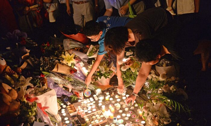 People light candles during a vigil at the site of a knife attack which left two children dead in Shanghai, China, on June 28, 2018. (- /AFP via Getty Images)