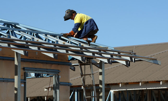 A welder works on the roof of a new house construction at Karratha in the North-West of Western Australia on June 17, 2008. (Greg Wood/AFP via Getty Images)