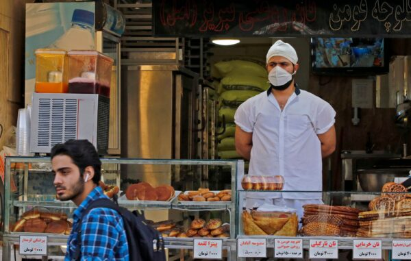 An Iranian man walks in front of a pastry shop